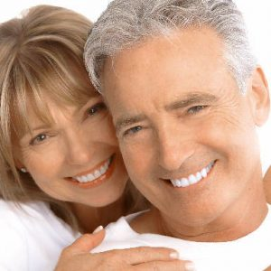 Smiling elderly couple who had done dental restorations work