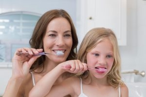 A mother teaches good oral hygiene practices